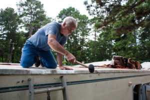 Dad hammering the edge of the new aluminum roof.